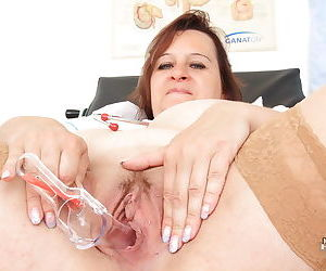 Mature gyno takes off uniform to expose her fatty body and examine her cunt