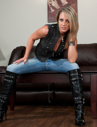 Tattooed tease Nikki Sims poses seductively in boots and black thong