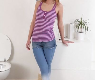Pretty hot young chick Liz is pissing and slowly undressing her pants