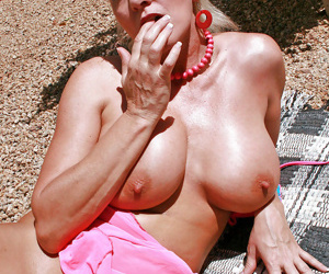 Sexy mature Cala Craves rubbing oil on her boobs and ass outdoor