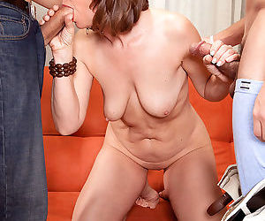 Over 50 lady Elle Denay lets her saggy tits hang while blowing 2 cocks at once