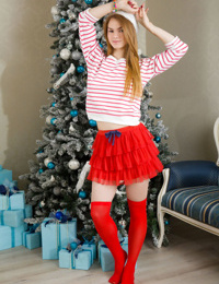 Sweet teen girl poses in red OTK sicks and a toque at Christmas