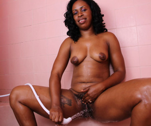 Middle-aged black lady Khrysie wet her hairy muff in the shower