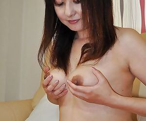Yasuko Yoshii stripping and masturbating her hairy cunt with a vibrator