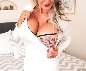 Petite granny Sally DAngelo enjoys showing off her big fake tits