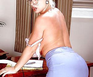 Glasses adorned mature pornstar SaRenna Lee freeing nice melons in office