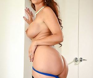 Middle aged lady Syren De Mer admires her big tits in a full-length mirror