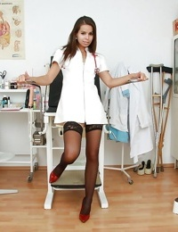 Foxy nurse in stockings stretching her cunt with a speculum
