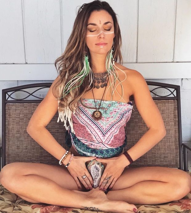 Yoga chick holding a rock in front of her skizz.