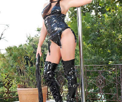 Weird princess in leather outfit and high boots on high heels fools around making a striptease