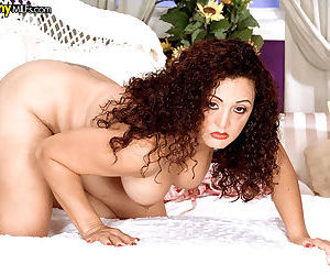Mature Latina housewife Melanie bares her big tits while disrobing on her bed