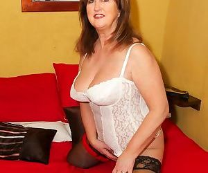 Middle-aged woman frees her tits and twat from white girdle in sheer stockings