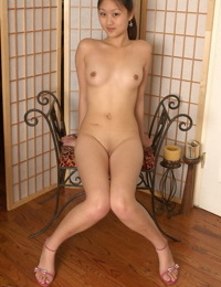 Asian girl in a short skirt sticks a finger in her pussy after getting naked