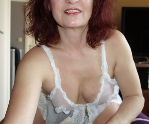 Older redhead Wanda slides white lace panties aside before sucking on a dong