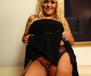 Older blonde Andrea plunges a couple fingers into her twat in sexy nylons