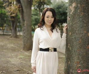 Classy Japanese female Yuna Yamami models non nude outdoors in a white dress