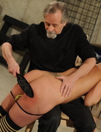Cute brunette in thigh high socks is paddled by and spanked by an older man