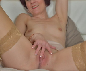 Short haired MILF over 50 Penny Brooks posing on bed in pantyhose