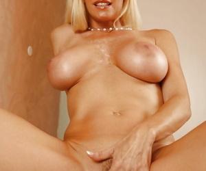 Full-bosomed blonde mature vixen undressing and spreading her legs