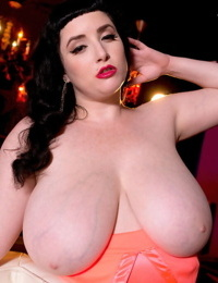 Dark haired BBW Jenna Valentine unleashes huge boobs as she strips naked