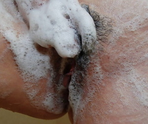 Naughty asian MILF rubbing her soapy curves in the shower