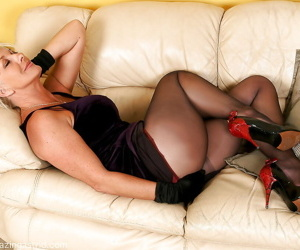 Hot mature blonde in pantyhose takes off her dress and poses in lingerie