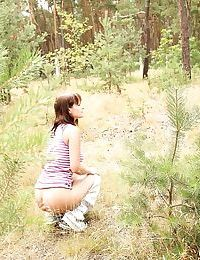 European teenager Rita E revealing nice tits while masturbating in the woods